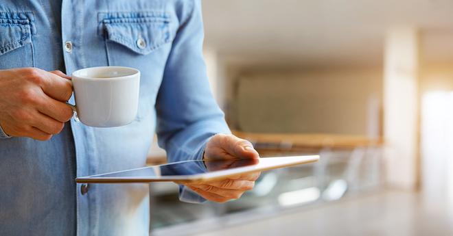 Guy drinking coffee looking at ipad
